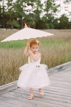 An umbrella that's bigger than the flower girl: http://www.stylemepretty.com/south-carolina-weddings/charleston/2014/10/15/summer-pastel-wedding-at-daniel-island-club/ | Photography: Jennings King - http://www.jenningskingphotography.com/
