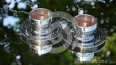 Mirror images of two filled coffee cups on transparent reflective surface.