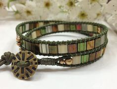 The colors of olive, green, gold, and cream in this Myuki Tila Bracelet capture the many shades of a lush forest. Accentuated with an Antique