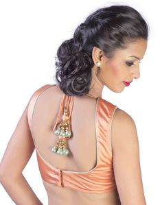 A peach satin blouse sheeting with turk piping accentuated with elegant tassel hangings.
