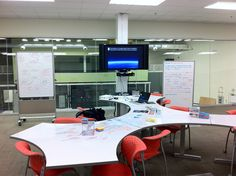 Whiteboard tables and chairs in front of a wall-mounted TV.