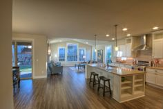 Open concept kitchen/living room.  Mosaic title back splash with white island cabinets.
