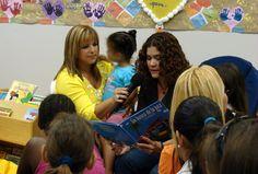 """First Lady of the Municipality of San Juan, Irma Garriga, holds the mic for Puerto Rican children's author Tere Rodríguez-Nora during a reading at the Casa Cuna de San Juan children's home in Puerto Rico. Tere Rodríguez-Nora was born and raised in Puerto Rico and moved to Orlando, FL in 2012. Her children's books include """"En Busca de la Paz"""", """"Kikiwi y los desperdicios en el fondo del mar"""" and """"Las estrella de los Reyes Magos""""."""