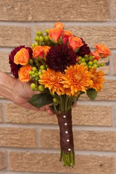Bridesmaids bouquets ~ combination of autumn cushion mums, burgundy dahlias, orange spray roses, green hypericum berries and foliage.