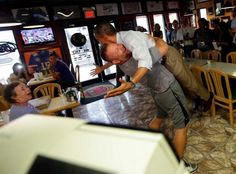 President Barack Obama, right, is picked-up and lifted off the ground by Scott Van Duzer, left, owner of Big Apple Pizza and Pasta Italian Restaurant during an unannounced stop, Sunday, Sept. 9, 2012, in Ft. Pierce, Fla. Photo: Pablo Martinez Monsivais / AP