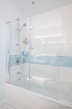 Projet de salle de bain réalisé par Claudia Bérubé Designer. Contemporaine, blanche, dosseret bleu géométrique, vanité sur mesure flottante avec poignées intégrées, comptoir de quartz, pharmacie et éclairage del.