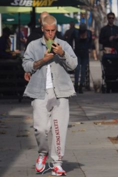 Justin Bieber wearing Vetements 'Eleven Inch Gun Club' Lounge Pants, Nike Air Huarache Ultra, Apple iPhone 7 Smart Battery Case