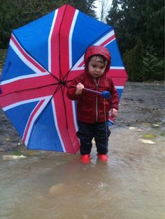 Child with umbrella in a puddle.  Hello, my umbrella is as big as I am!