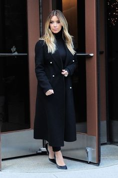 Kim looking chic in a simple black coat and blonde locks