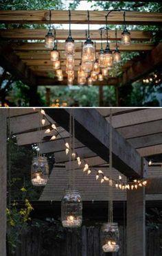 Wood and mason jars lighting are perfect for this cool backyard pergola. #outdoorlighting