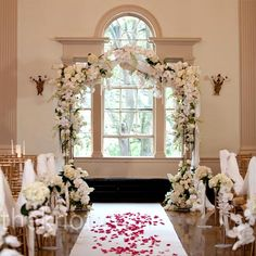 The focal point of the indoor ceremony was an arbor covered in all-white flowers and crystals.