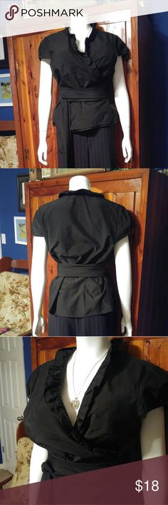 NWOT-Taffeta Ann Taylor Cross Front Blouse Sexy and cute black taffeta blouse. Criss-crosses in the front with an opening in the side of the blouse for tge waist tie to go through. Ruffles around the neck and front. Marked sz 18 but would better fit a size 16. Never worn and new without tags. Super nice! Ann Taylor Tops Blouses
