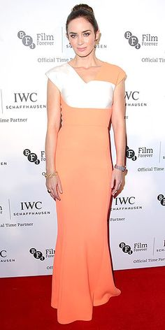 EMILY BLUNT  glows in a floor-grazing, coral-and-white colorblock Roland Mouret gown featuring subtly sweet details such as her neckline pleat and cap sleeves at the BFI London Film Festival IWC gala dinner.