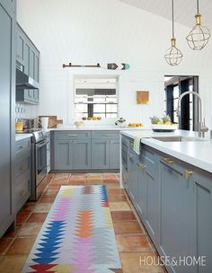 In this grey and white kitchen, a colorful runner breathes life into the space while contrasting with the Terracotta-tiled floors. | Photographer: Kim Jeffery | Designer: Virginie Martocq