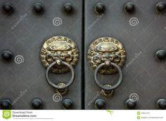 OLD CHINESE DOORS | An old golden Chinese door handle on a heavy metal door