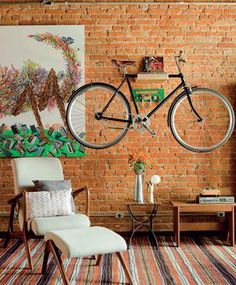 Choose natural colors, simple lines, modern furniture and add a unique art element like a bicycle, artwork or sign. This doubles as bike storage and looks great on the natural brick wall Bike Decorations, Range Velo, Bike Storage Solutions, Bike Shelf, Sweet Home, Bicycle Storage, Banquettes, Interior Decorating, Interior Design