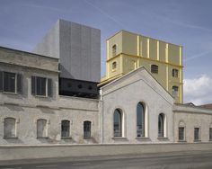 """The Fondazione Prada in southern Milan houses the fashion brand's namesake arts foundation, established by Miuccia Prada and Patrizio Bertelli more than two decades ago. Opened in May, the walled-in compound is a small city of culture, with a series of revitalized industrial buildings linked by de Chirico–like """"streets"""" and piazzettas. Image © Bas Princen - Fondazione Prada"""
