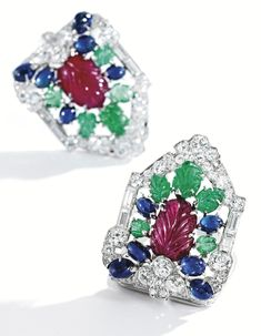 PROPERTY FROM THE COLLECTION OF MARIA MONET MARKOWITZ Pair of Platinum, Colored Stone and Diamond Clips, Tiffany & Co. The clips centering foliate clusters composed of carved rubies and emeralds accented by cabochon sapphires, within frames set with baguette, old European and single-cut diamonds weighing 4.85 carats; with a retractable jabot pin mechanism; late 1920s.