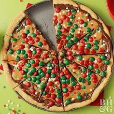 This cookie pizza is as versatile as you make it, to suit any holiday or occasion throughout the year. The crust of refrigerated cookie dough is topped with chocolate pieces, peanut butter, and assorted candies for a simple holiday dessert the kiddos can help with.