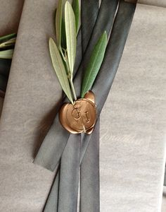 Embedded olive leaves and a wax seal adhere the ribbon
