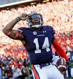 Auburn quarterback Nick Marshall (14) salutes after scoring against Alabama on a 45-yard touchdown run. (Dave Martin/AP)