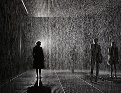 """Members of the public experience the """"Rain Room"""" art installation by Random International at the Barbican Centre in London. The """"Rain Room"""" is a 100 square meter field of falling water that visitors are invited to walk into, with sensors detecting where the visitors are standing."""