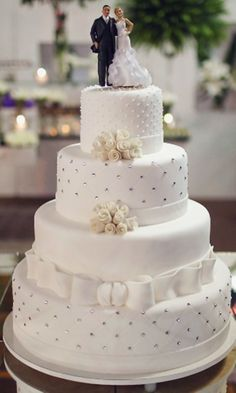 "Classic creamy white cake with quilted design and bow. This is for the main cake tier (#4). Customized changes include: creamy white fondant icing, white bow, ""diamond"" ribbons on other layers, red roses, white ceramic couple topper. Simple elegance."
