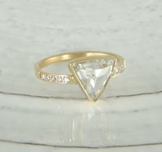 This ring features an amazing clear rose cut diamond set in a handcrafted bezel setting. Set alongside either side of the center diamond are 5