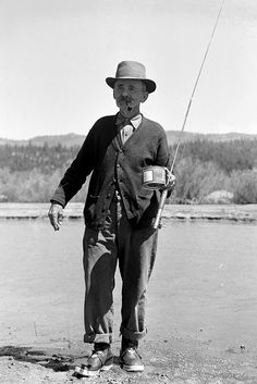 """A fisherman carries his fly pole and can of bait in Idaho City in 1939. Photo by Everett """"Shorty"""" Fuller, courtesy Idaho State Historical Society."""