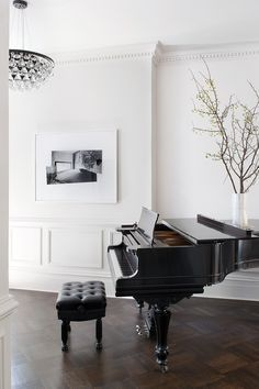 ochre drop crystal light + baby grand piano + branches + parquet flooring + white walls