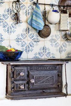 Cast iron antique kitchen stove with beautiful tiles behind. Vedspis, Växö, Sweden.