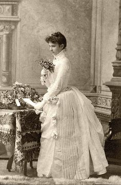 Woman with Flowers, 1880s love the dress but glad we don't wear the layers any more (does this dress make my butt look big)