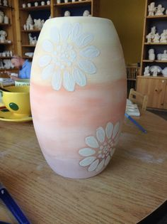 Orange ombré painted vase with white flowers that I painted at color me mine.