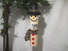 A snowman ornament made of two recycled wine corks. His hat brim is made of felted wool and he sporst a plaid hat band and scarf. Measures about 4