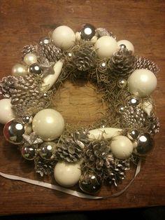 Een krans versierd met kerstballen en dennenappels (zilver gespoten)