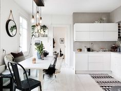 Home tour: un appartement Suédois plein de caractère au charme féminin. Cuisine noire et blanche, avec un grand tapis ethnique.