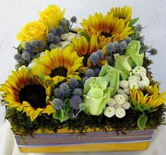 This pave floral arrangement is great for the outdoors. It has sunflowers to complete the summer look, roses, and button mums. Modern Floral Arrangements, Flower Arrangements, Sunflowers And Roses, Sunflower Centerpieces, Modern Floral Design, Corporate Flowers, Flower Show, Flower Boxes, Floral Bouquets