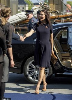 The Tasmanian-born Royal wore a classic knee-length navy blue dress and a brooch with tan clutch from www.CarlendCopenhagen.com