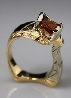 1.28ct Dreamscape™ cut Orange Tourmaline by John Dyer & Co. 1st Place Award winning design in the Wisconsin Jewelers Association Awards in the Women's Jewelry under $2,000 category. Ring made with 14k White and Yellow Gold, Diamonds and Sapphire accents with hand engraving by Jake Bauer of Bauer Jewelry Designs.