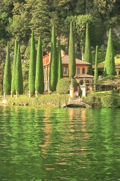 Villa and cypresses reflected in Lake Como (Italy)
