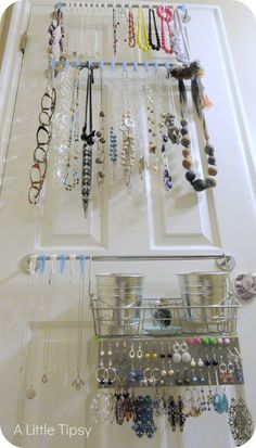 A Little Tipsy: DIY Jewelry Organizer - a whole system mounted on the back of a bathroom door, with one rod and plastic s-hooks for short necklaces, another for long necklaces, and a third rod with a basket with buckets for bracelets and rings and also a peg-style earring rack