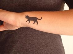 Black cat tattoo on the woman arm