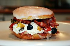 Creamy Bacon Donut: Pictured is a glazed donut split as a sandwich bun, filled with bacon, cream, blueberries, pineapple pieces and strawberries.