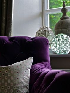 """Modern Classic sitting room, with cushions in aubergine velvet, and fuchsia and aubergine spots on a  taupe silk background. Aubergine velvet armchair """"Mr Bright"""" by MultiYork. Concrete pot and glass paper weight accessories from OKA Design by Sarah Gordon Home"""