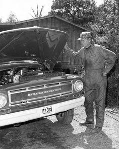 John Wayne Looks under Hood of International Truck