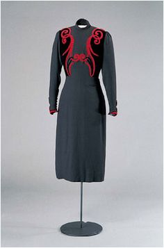 """""""This dress is part of the last order of clothes Queen Maud made from Worth before her death 26 November 1938 at the age of 68. The original design for 'Flirt' survives in the Worth archive in the V Museum. Comparing the two, it is clear that the wide shoulders fashionable in the late 1930s were not to Maud's taste. Nevertheless she obviously liked the striking design of Rococo style scrolls appliquéd in black velvet and red on plain black silk. """""""
