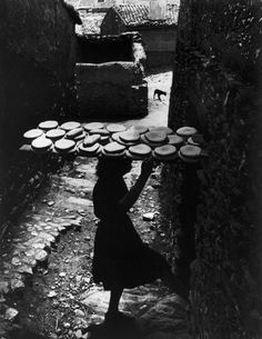 """W. Eugene SMITH :: Girl carrying 24 loaves of home made bread to the local bakery, in order to bake them / Deleitosa, Caceres, Extremadura, Spain, 1951 / from """"Spanish Village"""" photo-essay"""