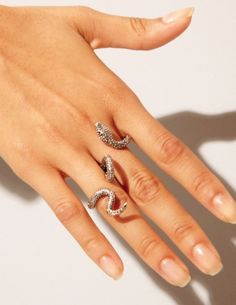 double finger silver ring featuring a textured snake that wraps around and in between two fingers. Adjustable.