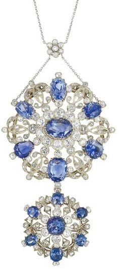 Belle Epoque Silver, Gold, Sapphire and Diamond Pendant-Brooch with Platinum and Diamond Chain The pendant-brooch topped and suspending two openwork circular plaques, one composed of a scrolled garland motif and the other of geometric wirework design, both centering and encircled by 14 oval, pear and cushion-shaped sapphires approximately 46.50 cts., set throughout with 89 old-mine cut diamonds approximately 7.25 cts., completed by a platinum chain cinched with a diamond-