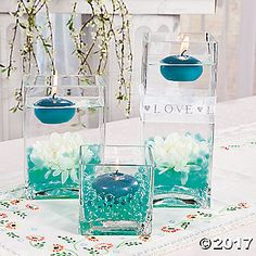 Add accent lighting to your reception tables with this simple idea that makes a big impact. Fill clear square vases of varying heights with water beads that ...